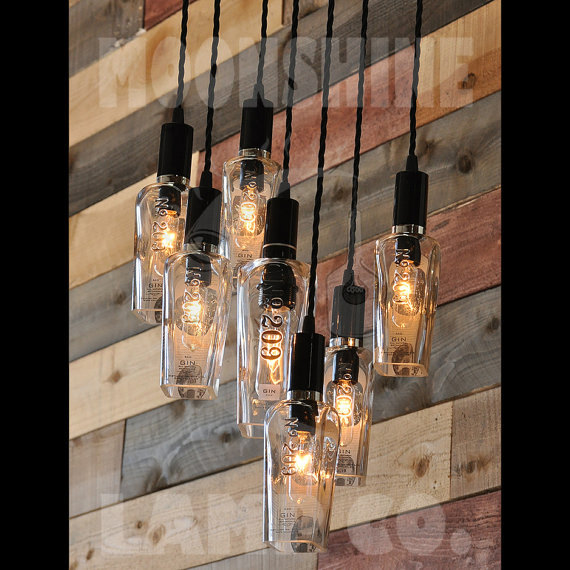 This is a chandelier made from 7 209 Distillery Gin bottles. The big bottle in the center takes a tubular bulb with a medium base socket . The surrounding smaller bottles take a candelabra base tubular style bulb. The fixtures are wired with vintage style cloth cord, and the 24 ceiling canopy is made from wood and metal. I can make this chandelier with many different kinds of bottles, so please ask if you have a particular style in mind. You can also send me bottles of your choice if youd…