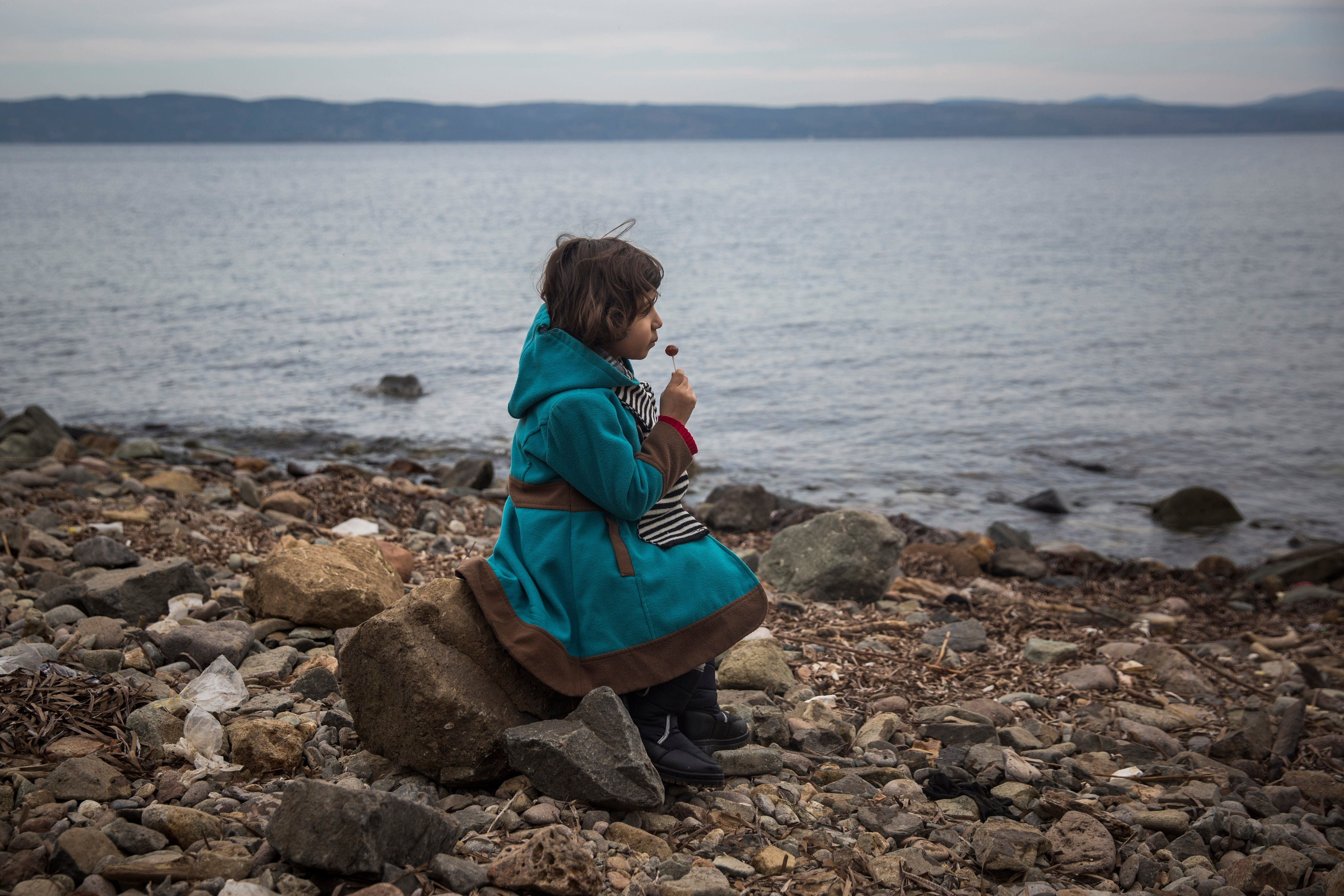 A Syrian girl eats a lollipop after her arrival on the Greek island of Lesbos on a small boat from the Turkish coast. The Greek authorities reported that 1,244 refugees have been rescued from frail craft in just three days this week, as thousands continue to arrive on the Greek islands Photograph: Santi Palacios/AP