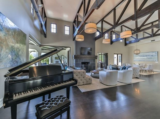 Dark wooden beams offset the cool grey palette beautifully. A large Yamaha piano is set to the side — perfect for when Britney entertains guests.