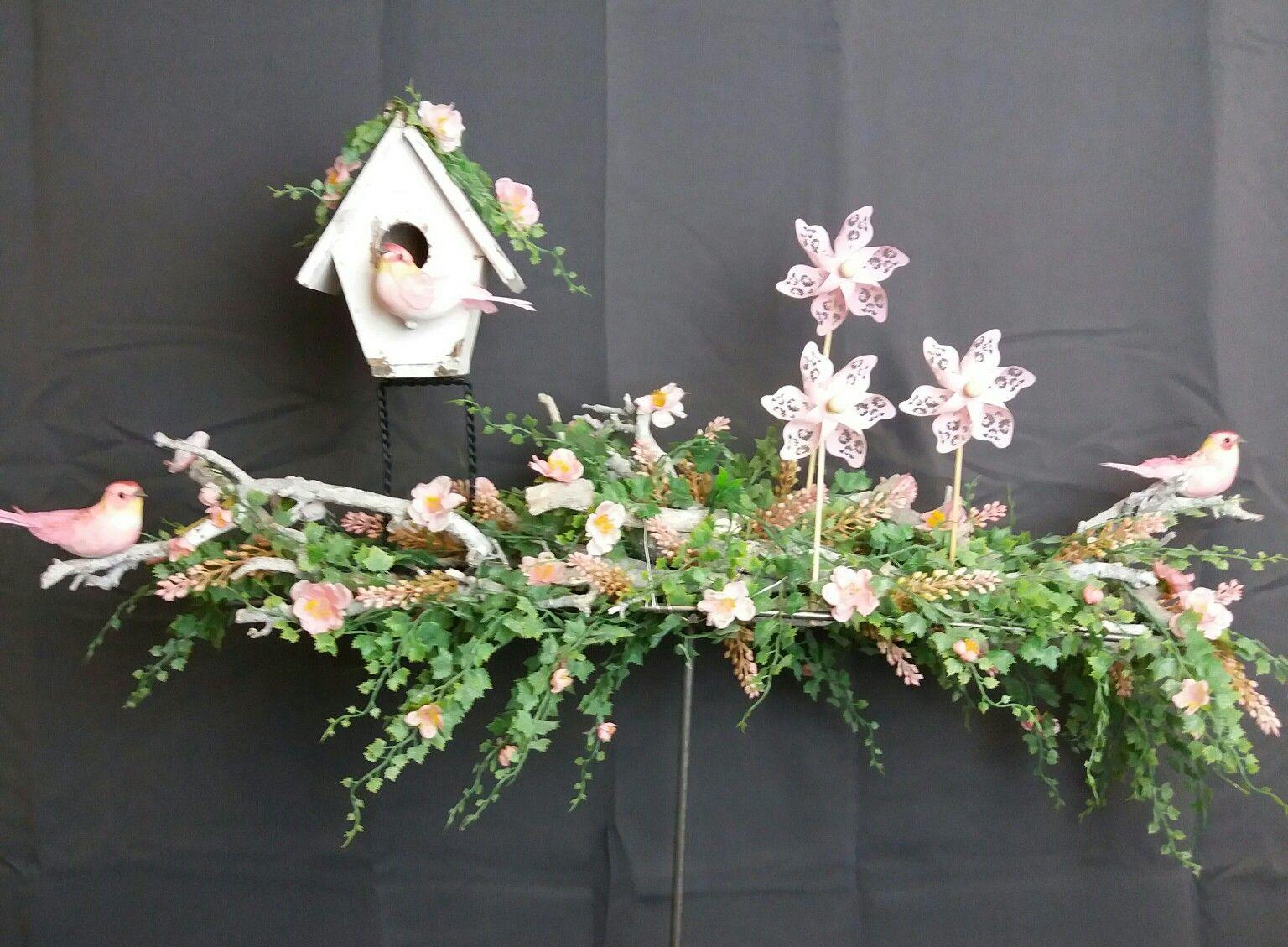Zomerdecoratie. Frame met vogelhuis op poten. En echt draaiende windmolentjes