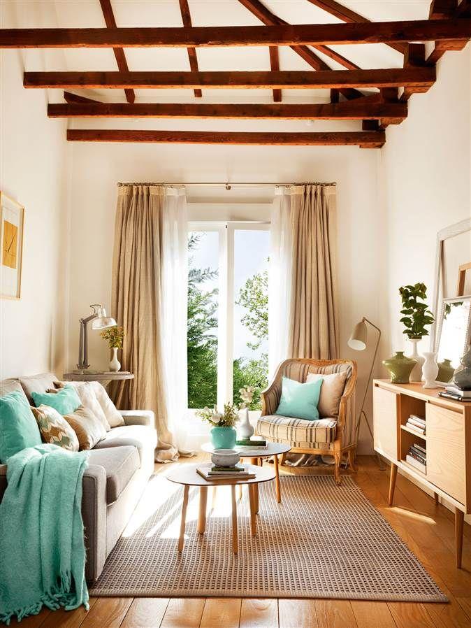 Salón pequeño con vigas de madera vistas, sofá, butaca y dos mesitas ...