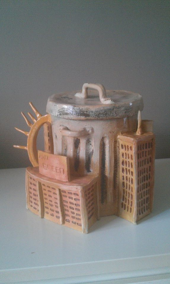 """""""Polluted"""" This is a conceptual teapot completed to exemplify the issue of global warming. The center that contains the water is a garbage can and the spout connected to it is a smoke stack. Circling the can are four buildings that represent a city in ruins. Finally, the second most important factor in global warming, heat, is exemplified as a sun which makes up the handle of the pot."""