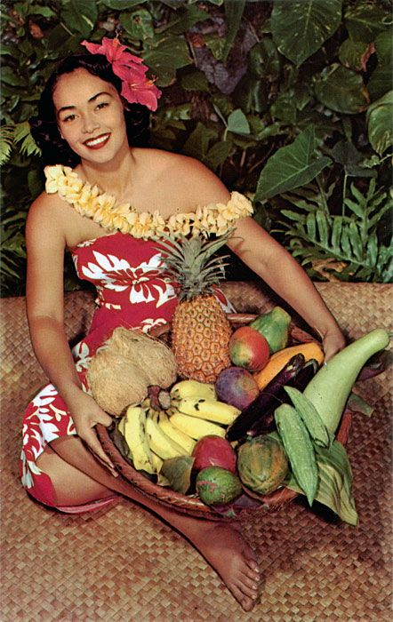 Hawaiian fruits and vegetables identified from top, clockwise: Pineapple, papaya (green and gold), mangoes (red blush), egg plant (dark purple), Chinese preserving melon (pale green, smooth), bitter melons (light green, crinkled), avocado (dark green at bottom), bananas, and husked coconuts.  In her hair, the girl wears red hibiscus, Hawaii's official flower; the lei is of plumeria or frangipani.