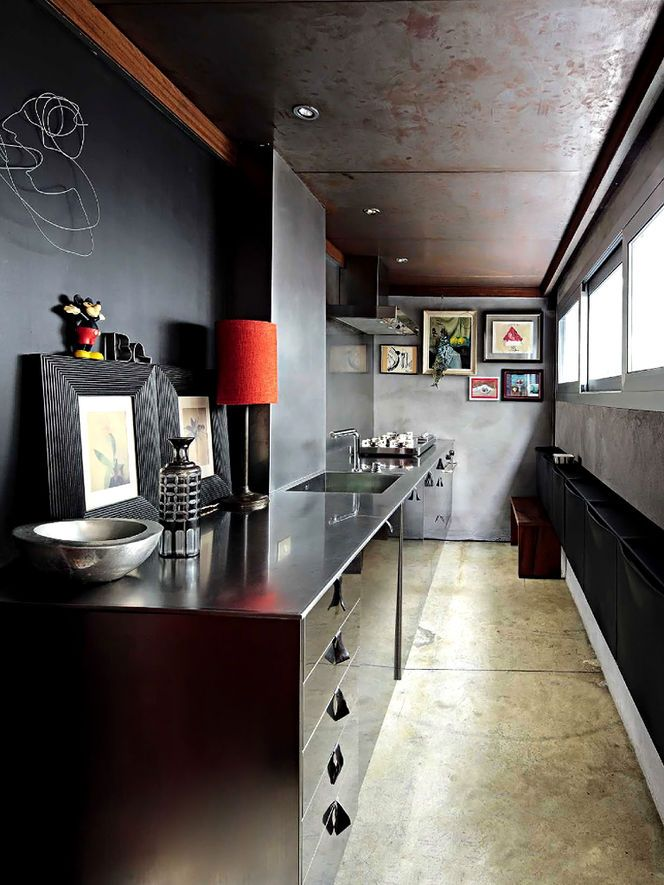 This contemporary black kitchen, designed by Italian architect Piero Gemelli, combines high shine (the lower cabinetry) with matte finishes (blackboard and concrete). The walls may be clad in metal, and the ceiling certainly seems to be. A pair of botanicals that are framed in wide black wood lean on the counter, while a colorful selection of paintings are clustered on the far wall.