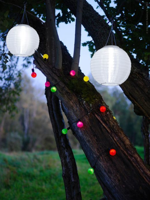 colourful lights wrapped around a tree via ikea garden. Black Bedroom Furniture Sets. Home Design Ideas