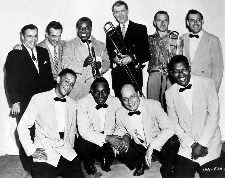James Stewart poses with the jazz greats who appear with him in The Glenn Miller Story. Top: Ben Pollack, Gene Krupa, Louis Armstrong, Stewart, Murray McEachern and Babe Russin. Botttom: Trummy Young, Cozy Cole, Barney Bigard and Arvell Shaw