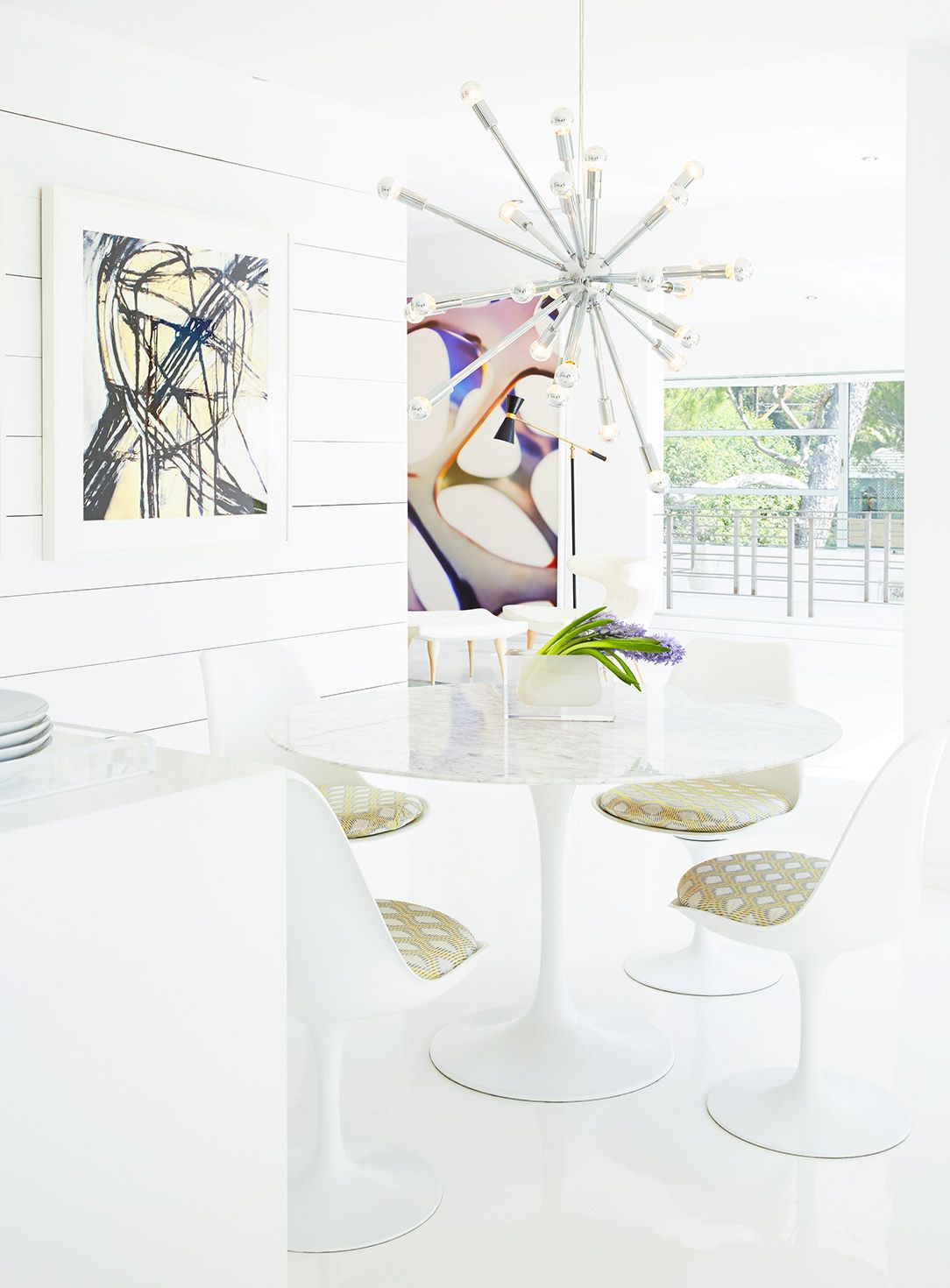 Modern midcentury dining space with all-white color palette and beautiful artwork