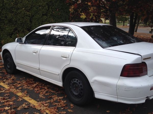 White Mitsubishi with tinted windows, black rims, power windows, really good AC and heater, with 202,452 miles.