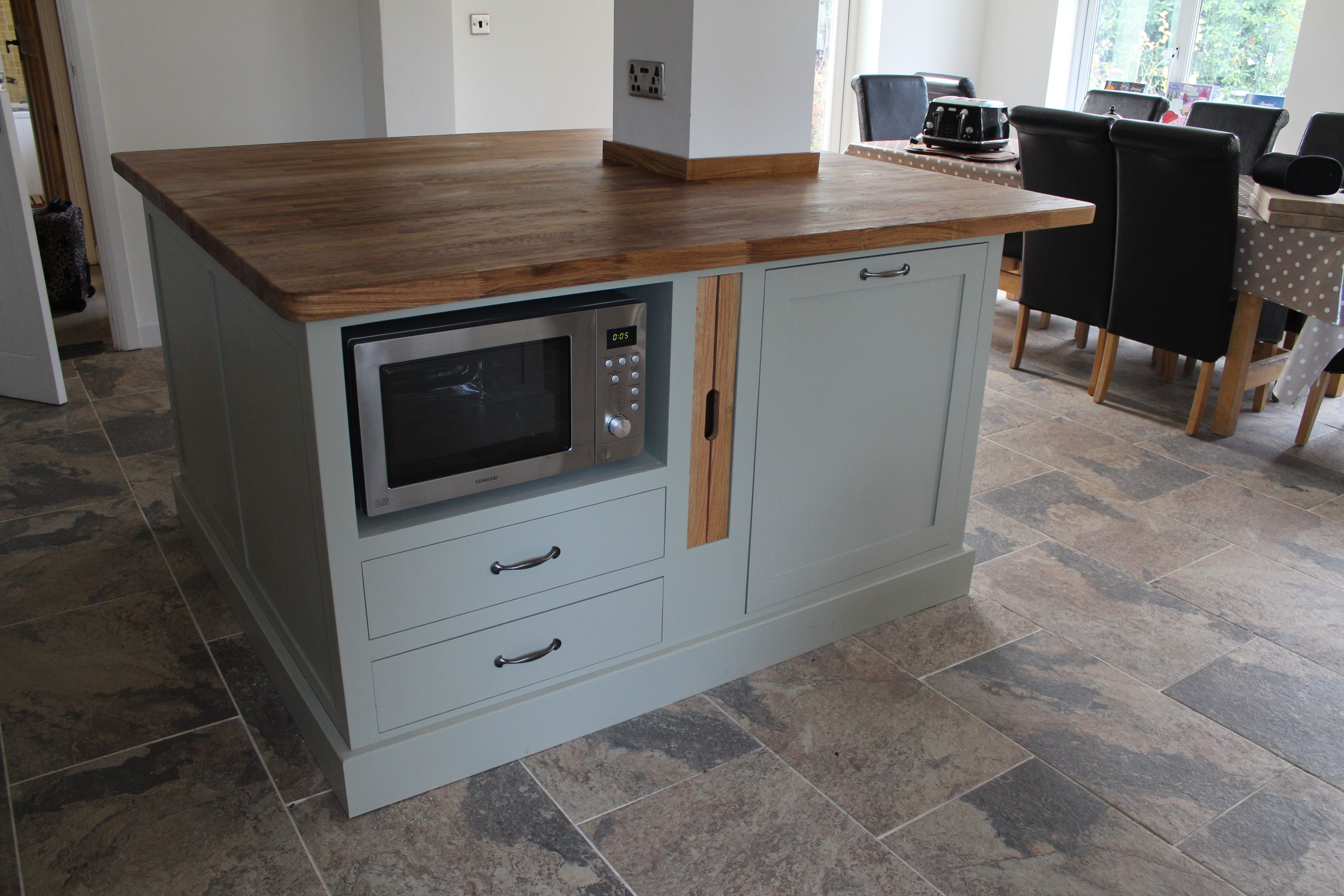 A kitchen island built around a pillar with a microwave on