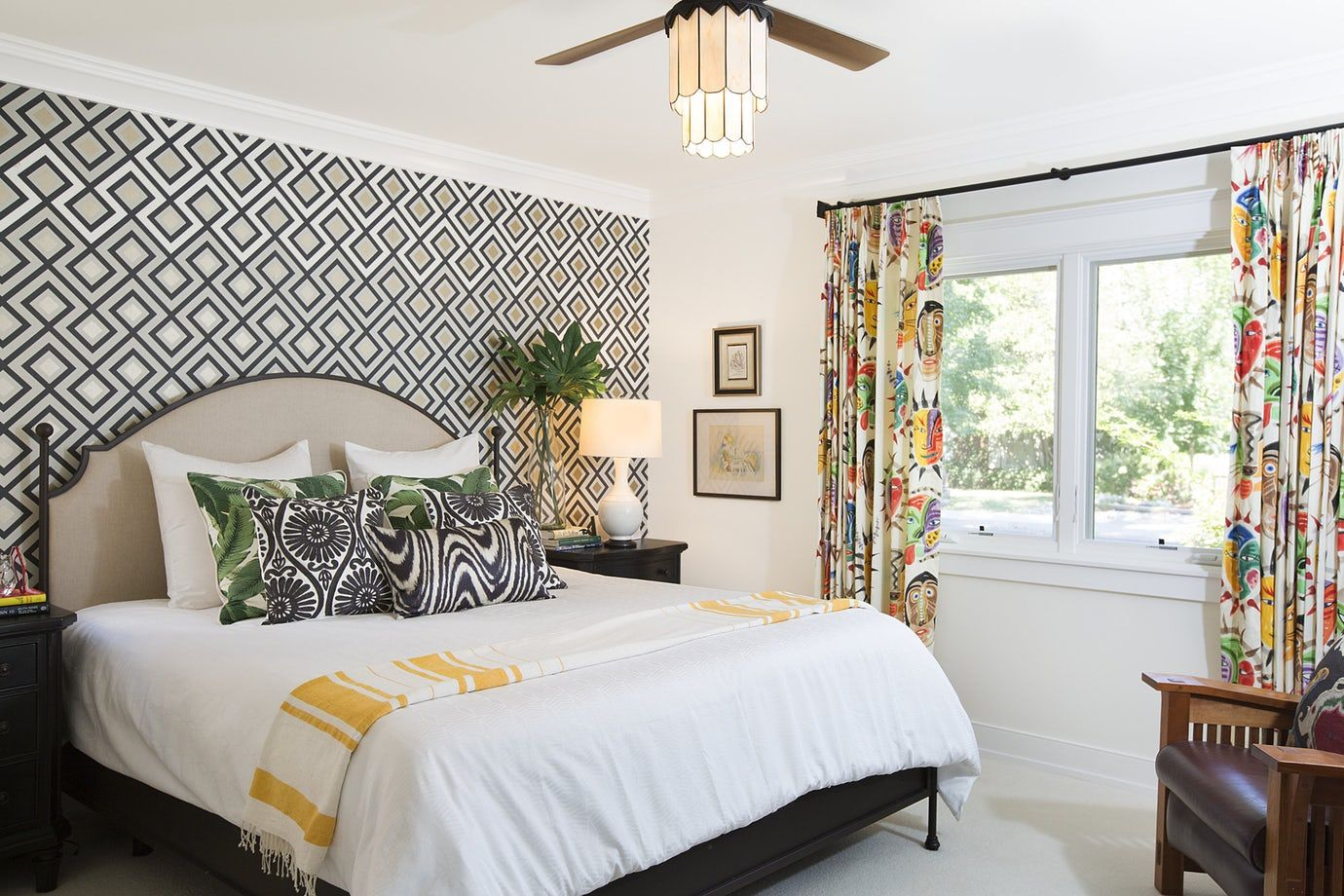 Accent wall with geometric wallpaper and colorful drapery ...