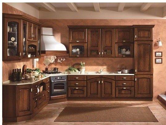 Cucina in legno scuro con cappa darredo bianca e vetrine