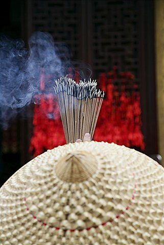 Chinese woman with incense sticks, Jade Buddha Temple, Shanghai, China