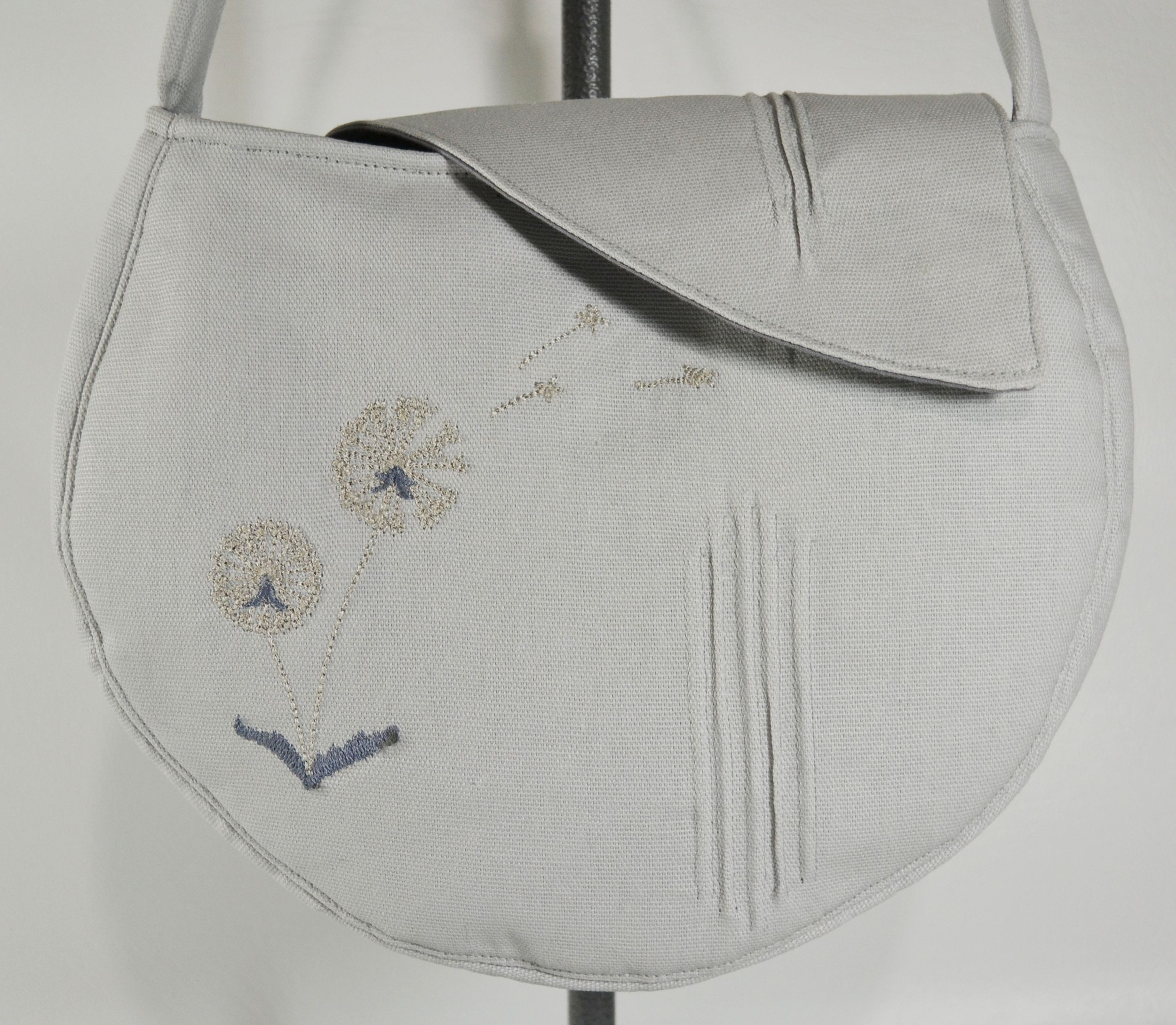 Emma Purse in Stainless Dandelion features an embroidered dandelion and heirloom pin-tucks.