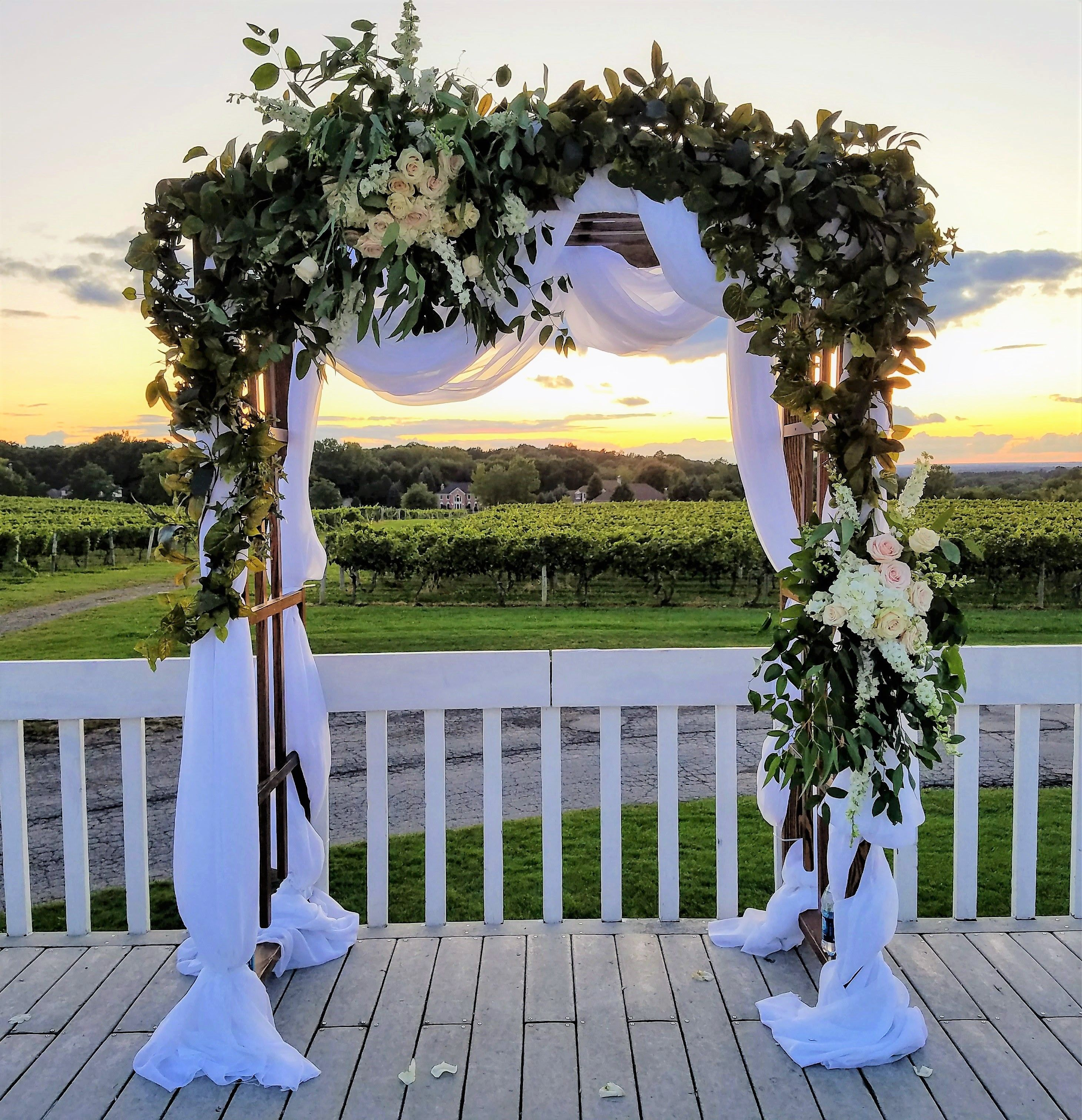Our rustic arch with draping greenery and floral party