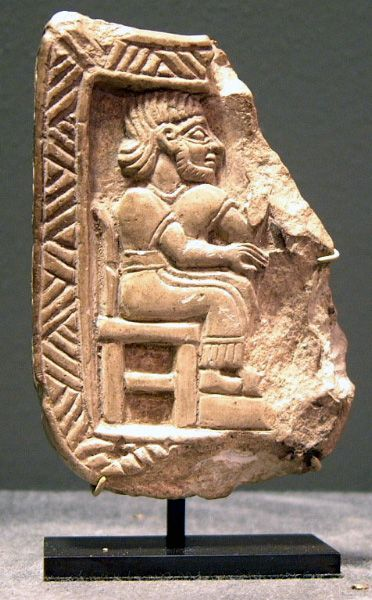 Babylonian stone relief sculpture depicting a seated