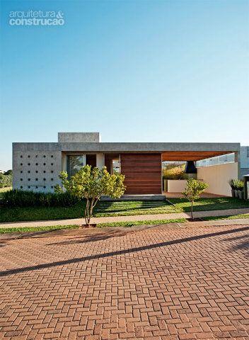 De 5 m, o recuo frontal configura uma calçada permeável, aberta para a rua. Na fachada, o trecho de concreto vazado protege a cozinha. Projeto Drucker Arquitetura.