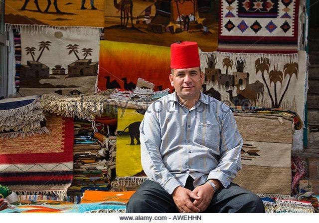 Egyptian man selling carpets in souk in Old Sharm Sinai Egypt - Stockbild
