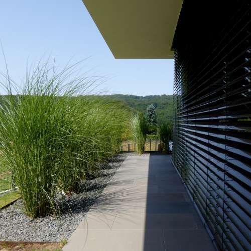 Minimalistische Gartengestaltung am Hang mit Wasserbecken aus Cortenstahl und Feuerstelle | #sichtschutzfürbalkon