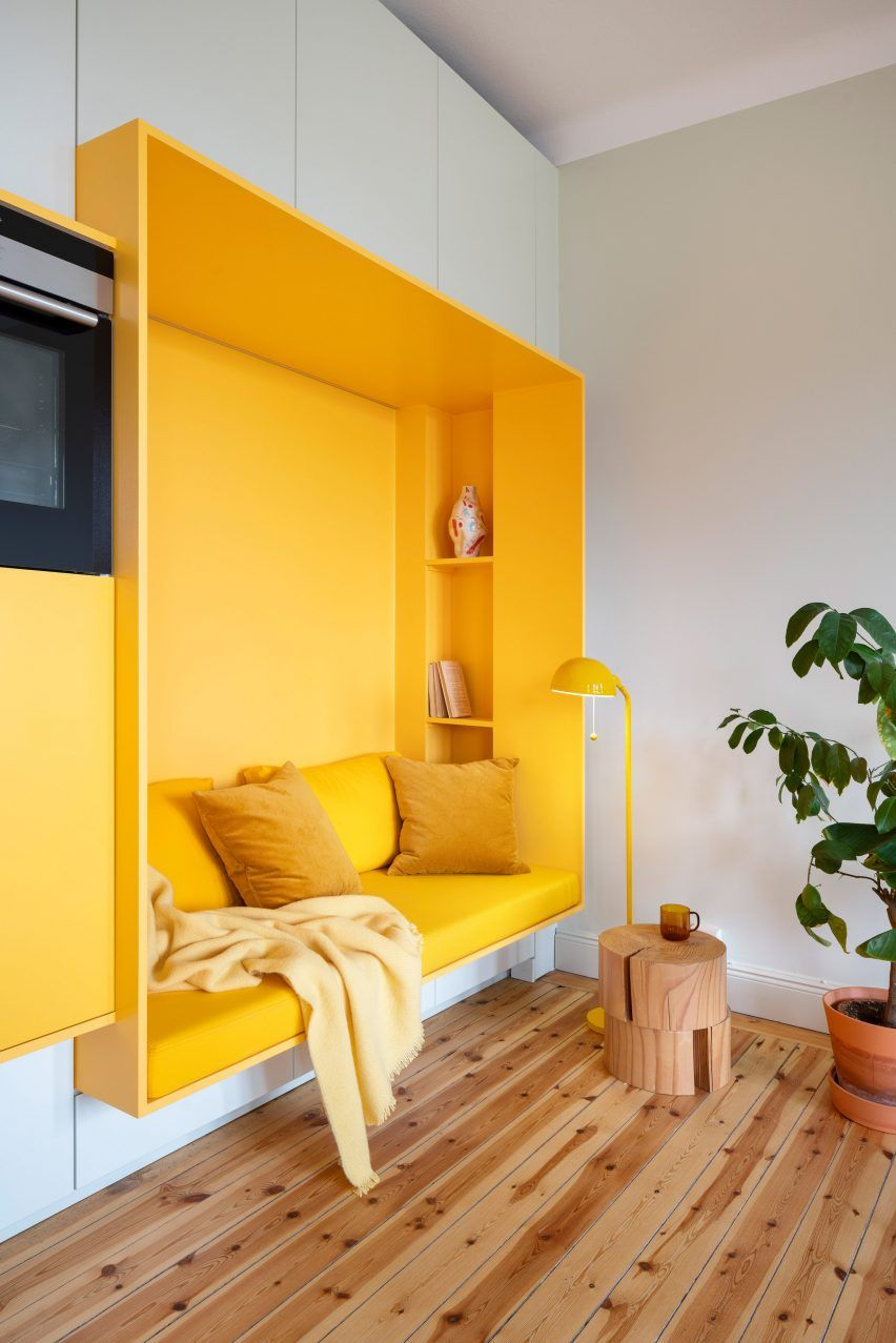 Storage walls define space within bright yellow apartment in Stockholm #hallway
