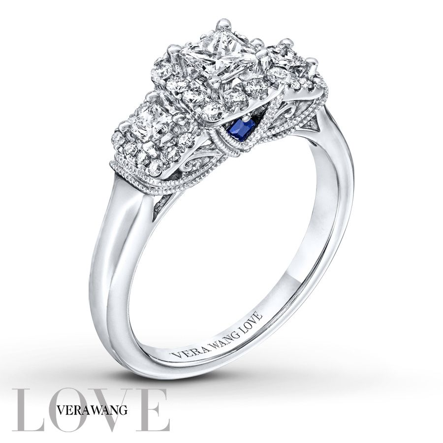 From the Vera Wang LOVE Collection, this captivating 3-stone diamond engagement ring features a trio of princess-cut diamonds. Set beneath the bezel of the largest stone are two princess-cut sapphires, the signature of the collection and symbol of everlasting love. Round diamonds accent the ring on all sides, ensuring sparkle from any angle and completing this exquisite look. Set in 14K white gold with 3/4 carat total diamond weight, the engagement ring is a brilliant beginning to your r...