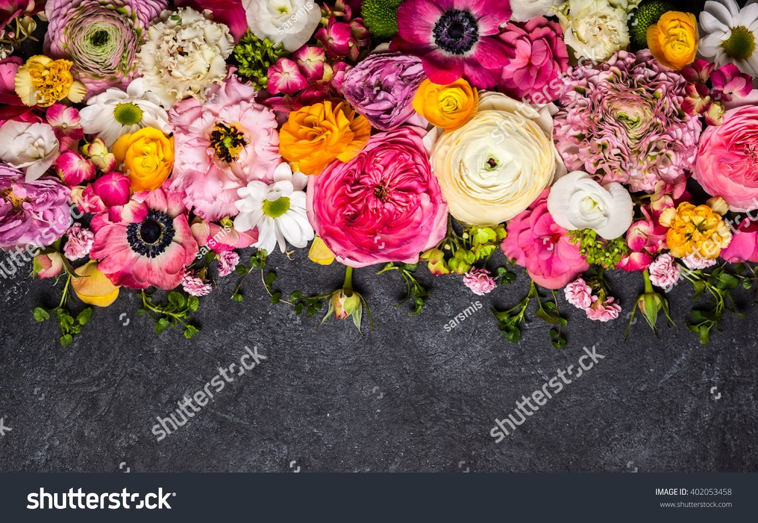 Various flowers on black background overhead view with copy space