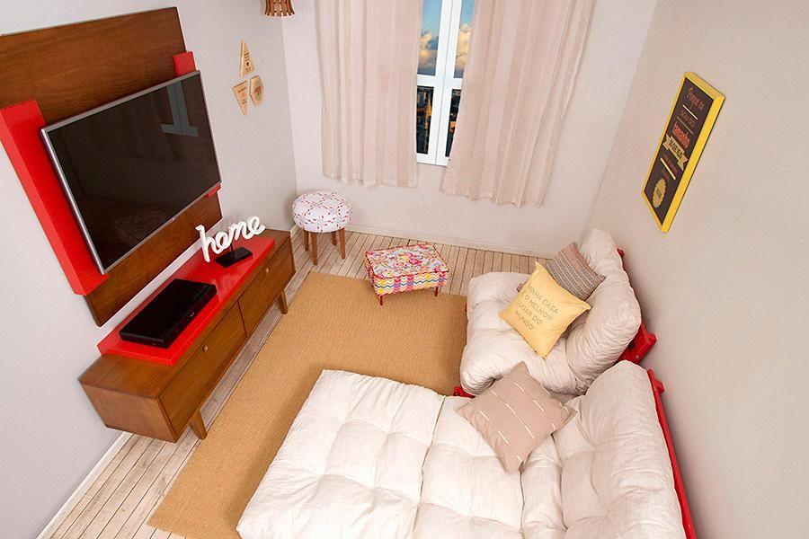 A sala de TV ficou aconchegante com o sofá de pallets e futons