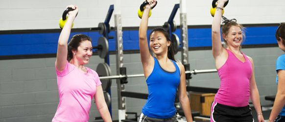 Three Young Women Training With Kettle Bells In Semi-Private Fitness  Training Session