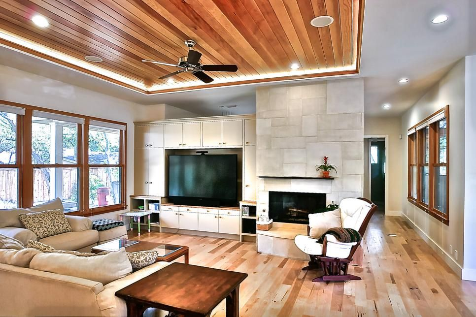 cove lighting highlights the wood paneled tray ceiling in this open