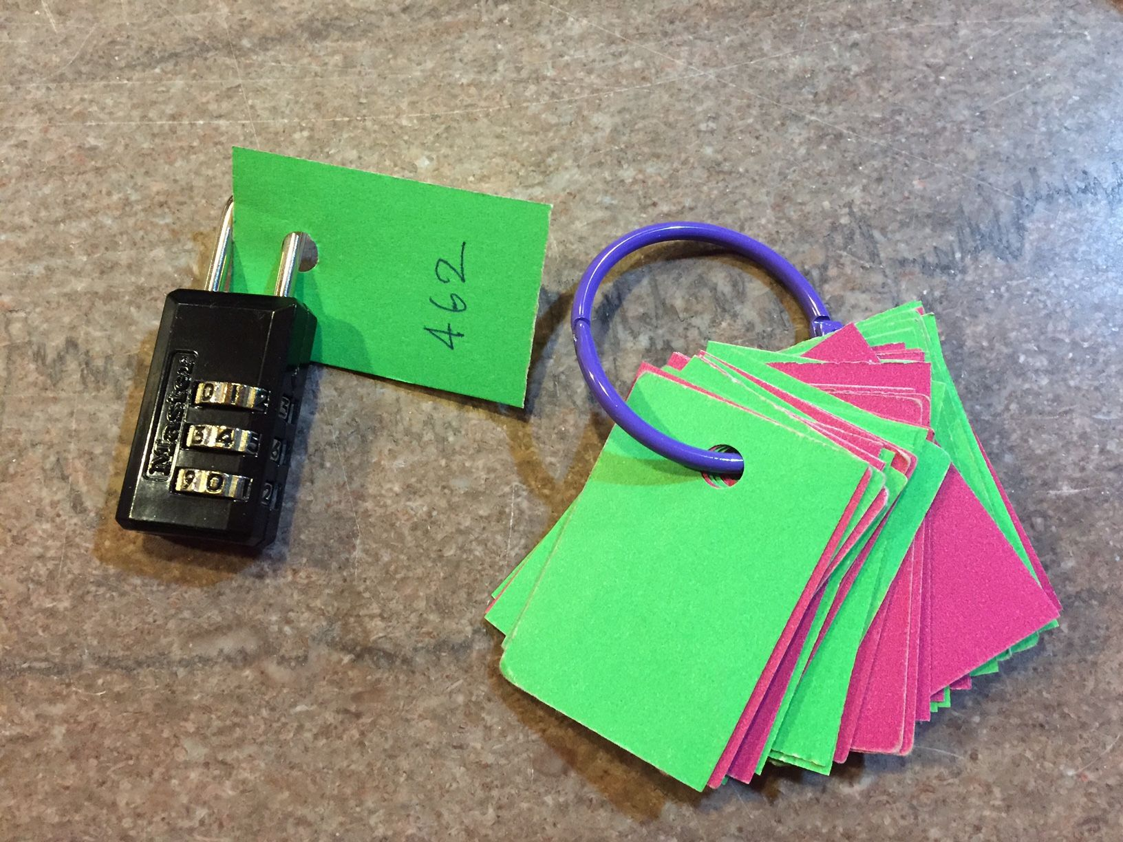 Ring of punched cards to record current combo and slip onto the shank of your lock as you pack up.