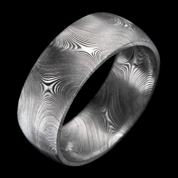 "Over a thousand years ago, ancient Syrian artisans forged swords of incredible strength and beauty. Andrew Nyce Designs wielded their techniques to create this ""Starlight"" Damascus stainless steel men's wedding ring with a dense, distinctive pattern of swirling cross-like stars. CustomMade.com"