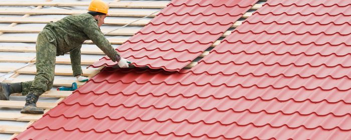 Man Laying Red Tile On A Roof