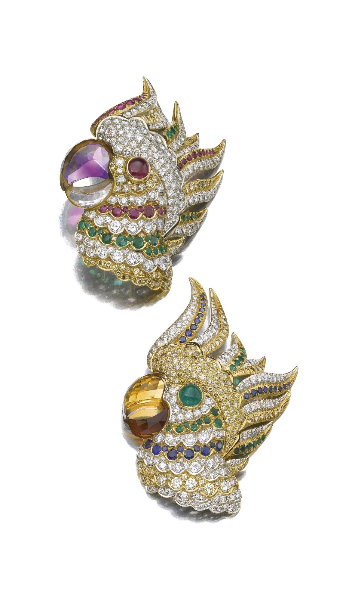 PAIR OF GEM-SET AND DIAMOND CLIP/BROOCHES Each designed as a parrot head with hinged feathers set en tremblant, one with a beak composed of faceted citrines, the head set with cabochon and circular-cut emeralds, and similarly cut sapphires and diamonds, the other with a beak composed of faceted amethysts, the head set with cabochon and circular-cut rubies, and similarly cut emeralds and diamonds.