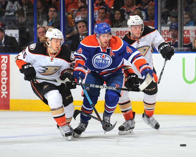 hot sales 57393 f9c22 Taylor Hall #4 of the Edmonton Oilers battles for the puck ...