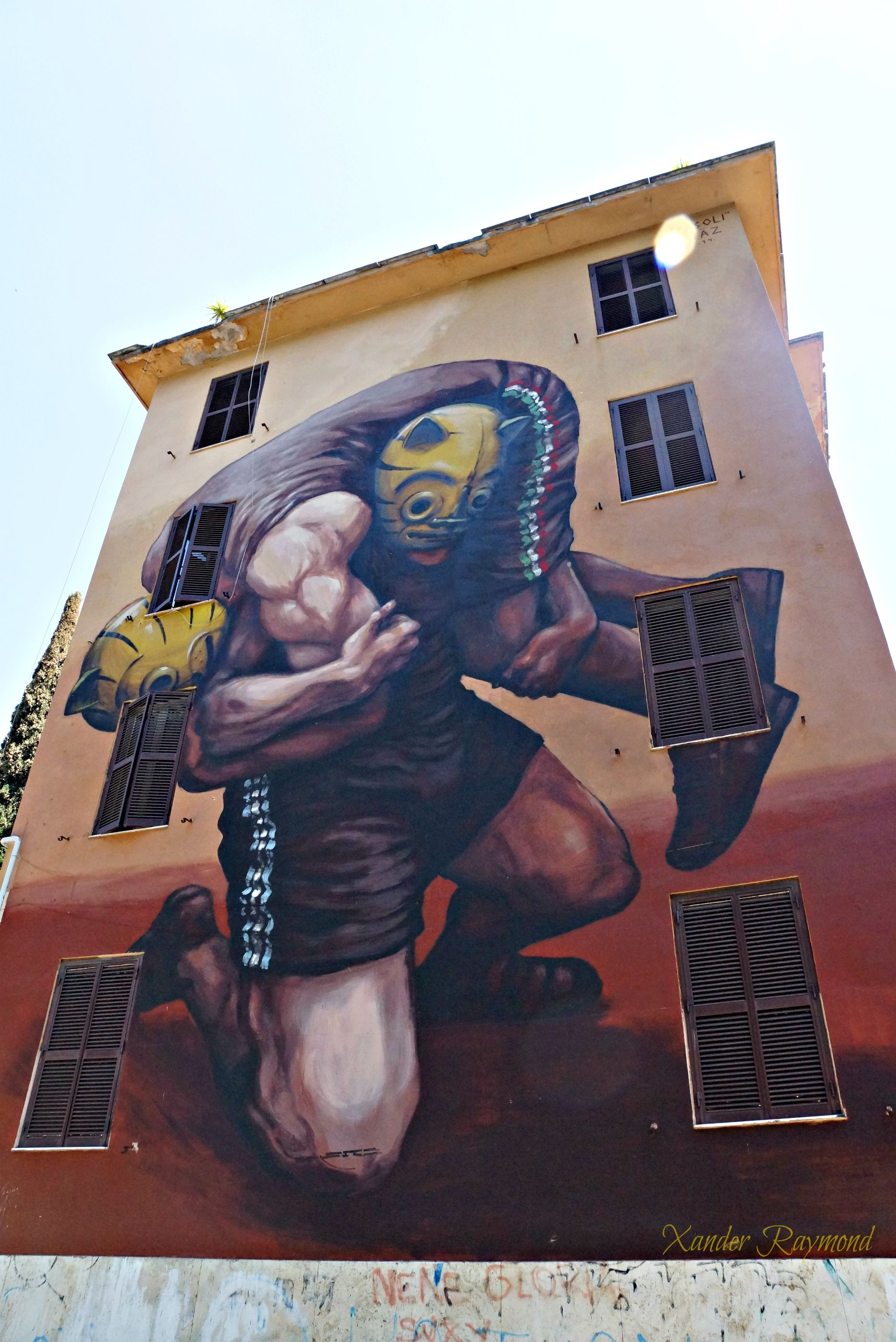 Image by Xander Raymond Photography, taken in Rome, Italy on a tree-lined street where many homes and buildings are covered with these beautiful murals