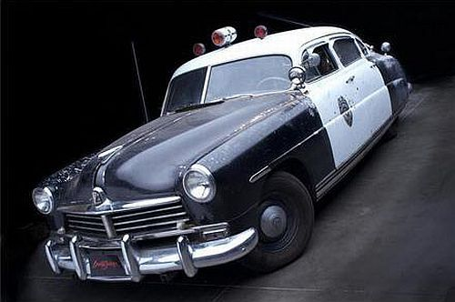 Use this image for discussing role of police in the novel, or cars in the 1950s in general