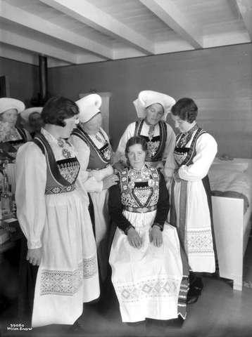 Galleri NOR; Hardangerbryllup Johan Larson Halven Gudveig Røte bruden klæder paa. 1933 Vossebunad