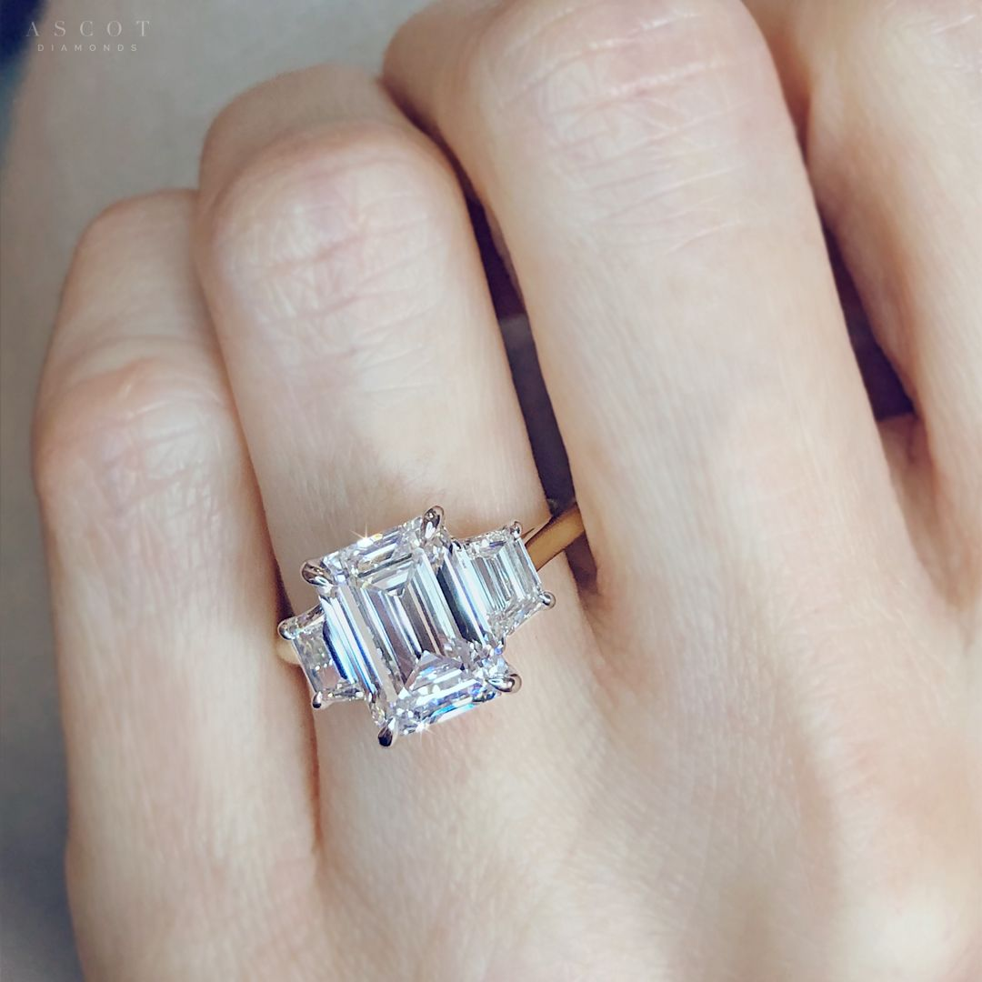 A custom design engagement ring feauturing an emerald cut diamond with matching side stones for an elegant and artdeco look. Learn more how to create the perfect diamond ring at Ascot Diamonds.