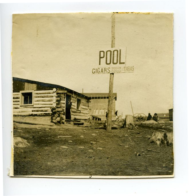 A photograph of a log building advertising pool and soft drinks.