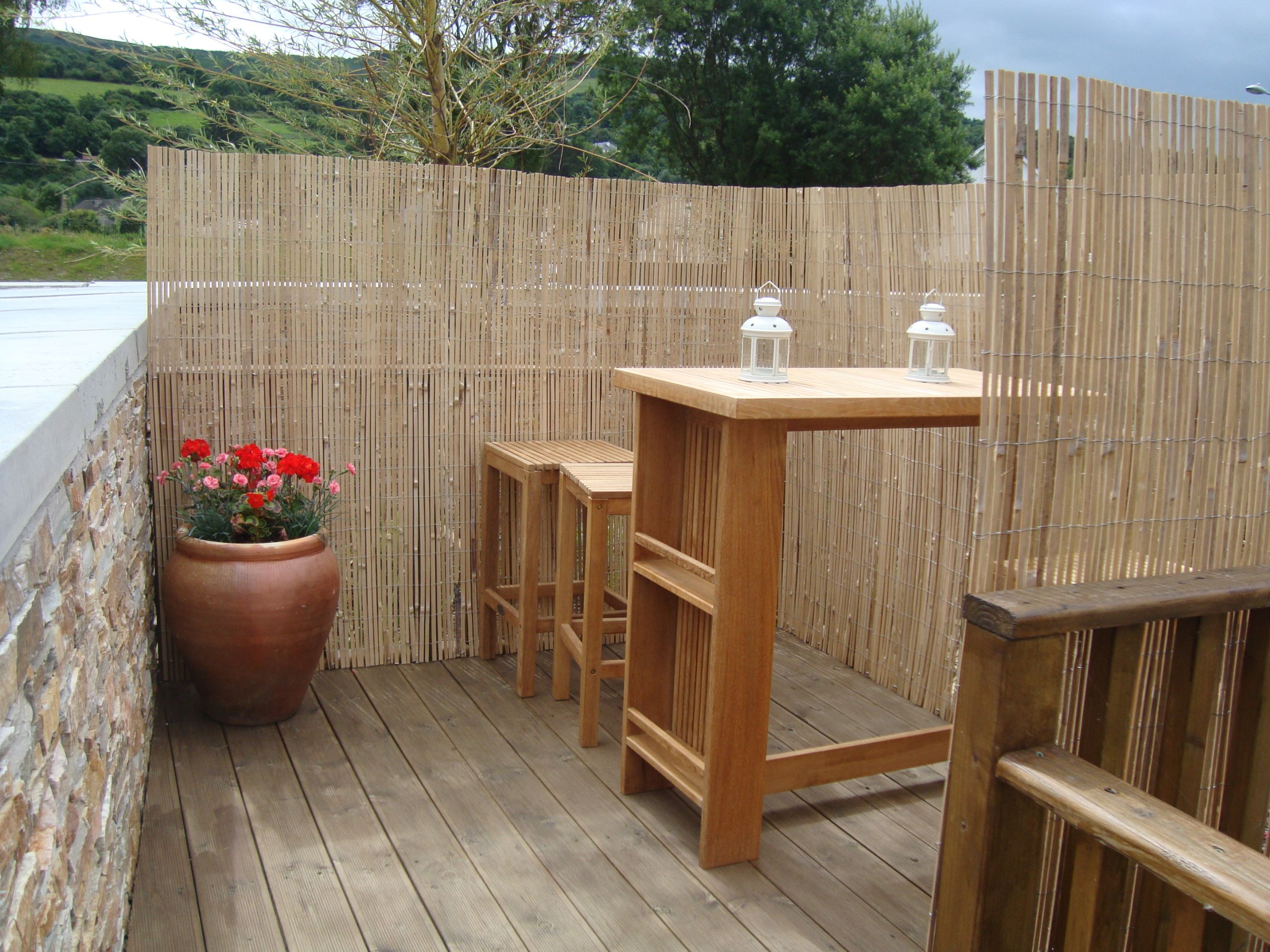 Outdoor beautify your backyard deck with split bamboo for Hanging privacy screens for decks