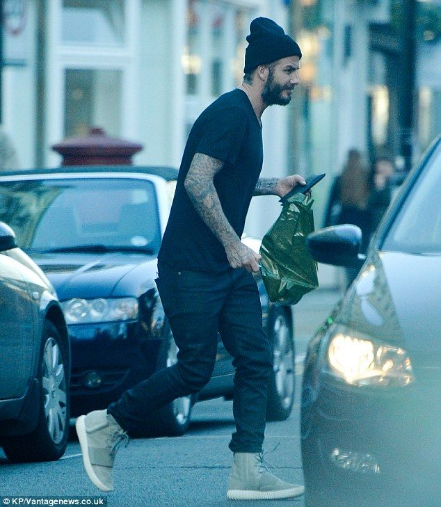 Casually cool: The husband of Victoria Beckham donned a black T-shirt and slim-cut jeans f...