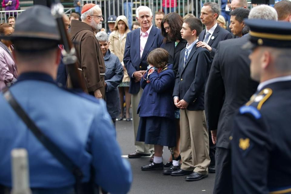 Cardinal Sean O'Malley (left) joins the family of Marathon bombing victim Martin Richard at the finish line for a wreath-laying ceremony.