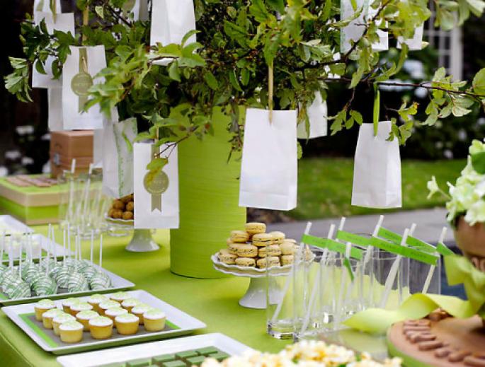 Decoración de mesa de postres en tonos verde y blanco para una boda al aire libre