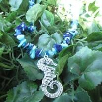 """This necklace features chunky dyed mother of pearl beads in shiny light blue and shiny dark blue. It has a detailed seahorse pendant and is the perfect summer necklace. This necklace is on the shorter side at 16"""" before the pendant."""