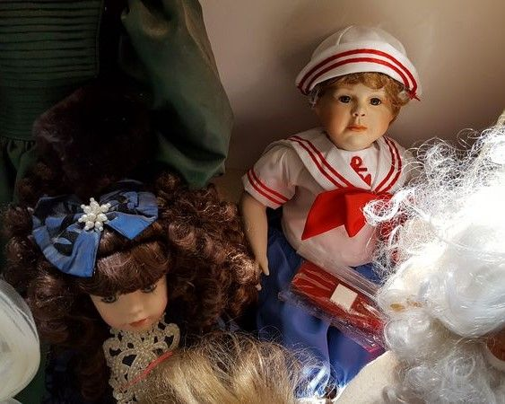 "Item # 2 -- Dolls & stuffed animals, some porcelain, approx 40 total, large & sm. Some boxes incl-see photos. Smallest doll approx 5""H (Japanese); tallest doll approx 28""T (dark green dresses). Located on 2nd floor. Incl dolls in lower shelving cubbies and on floor, shelving not incl."