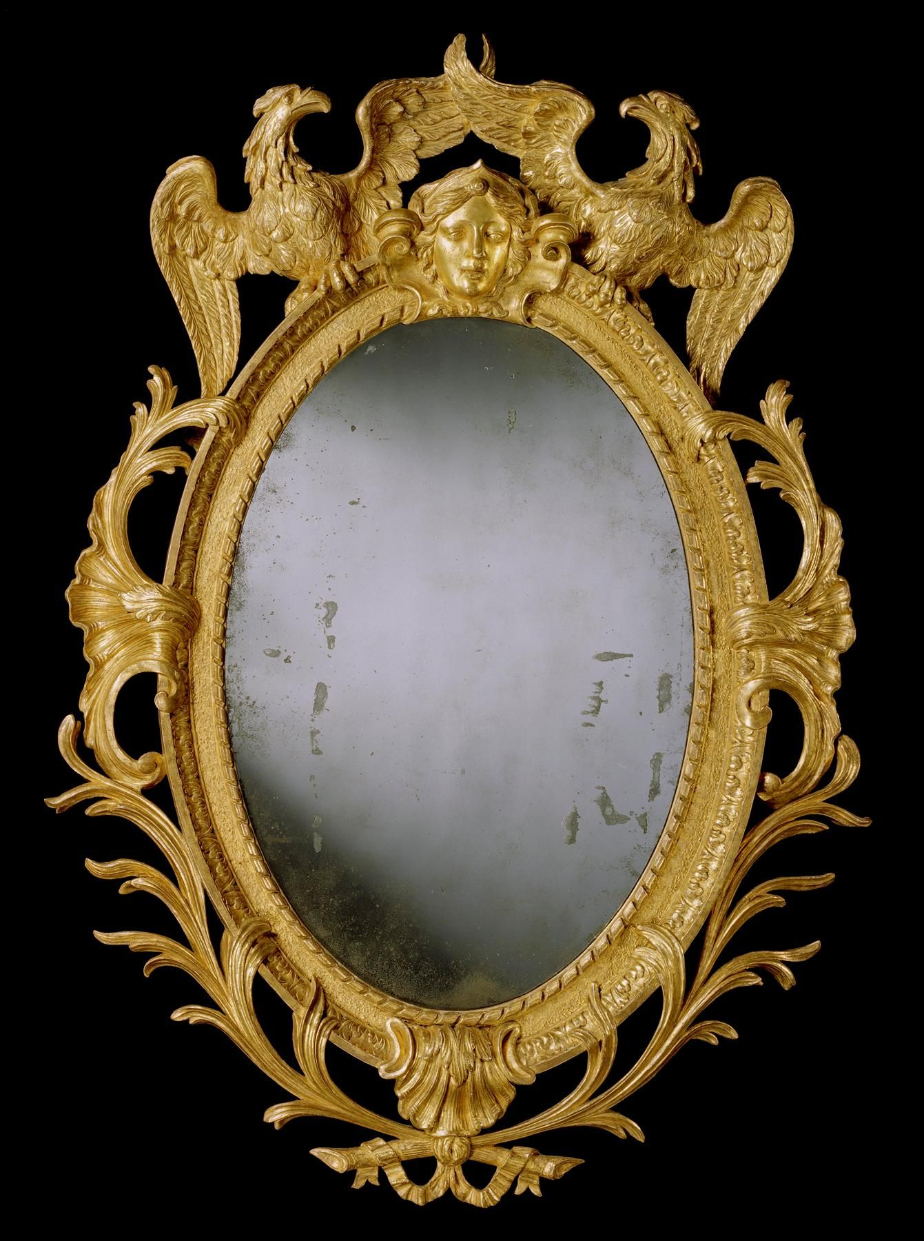 *A GEORGE II CARVED GILTWOOD OVAL MIRROR  A most unusual and rare mid 18th century carved giltwood oval mirror in the manner of William Kent. The replacement 18th century mirror plate having carved rope twist border and sanded surround with acanthus leaf moulding, centred by the head of Diana with cross-winged eagles either side and stylised shells on the sides with acanthus leaf scrolls, having further shell motif below, with ribboned palm leaf branches beneath.  English, circa 1740