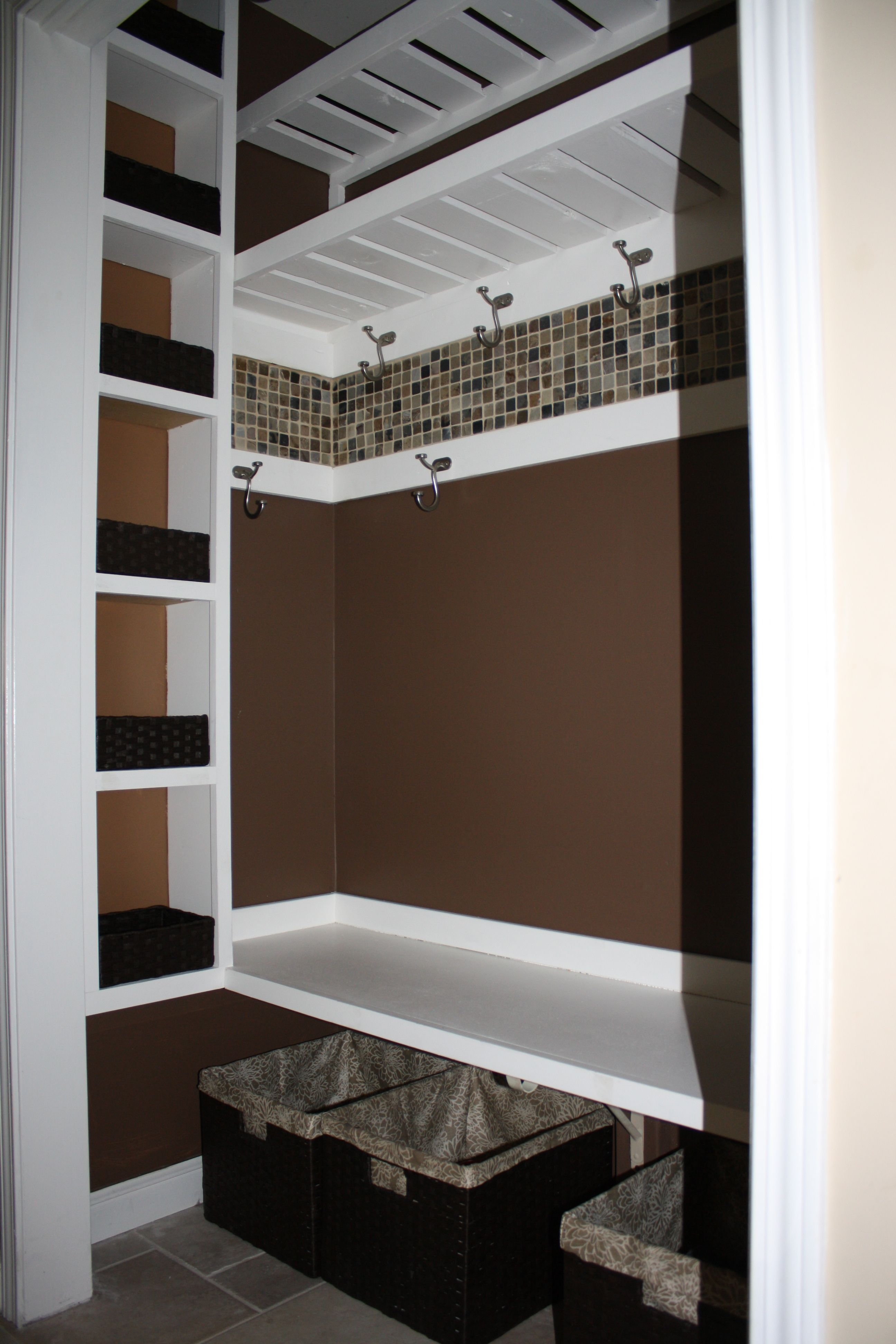 Front hall closet - I like the little shelves, bench, double row of hooks, and the border.  We have extra fireplace tiles!