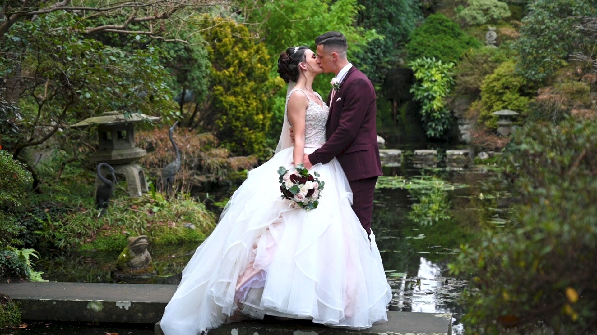 Married couple stood on a small bridge in the gardens of The Italian Villa