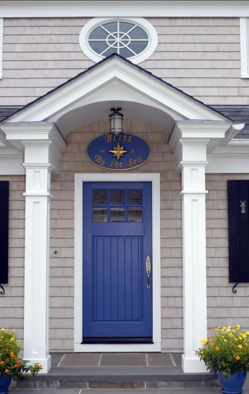 Oval sign over front door I like how it looks with the rounded roofline of the porch. bright blue front door colour on shingled exterior with 2 white posts and slate steps