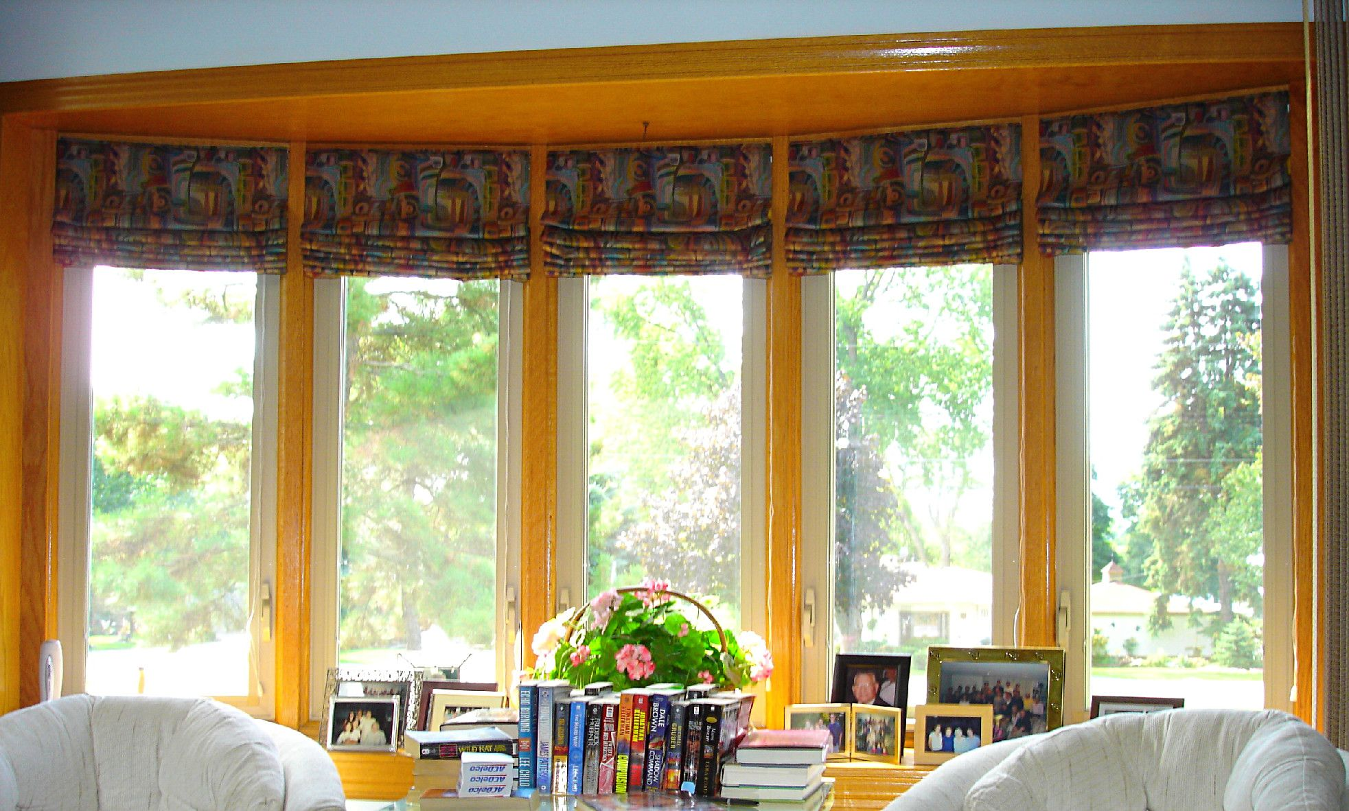 Roman shades in fabric inside the curve of this bow for Window treatments for a bay window