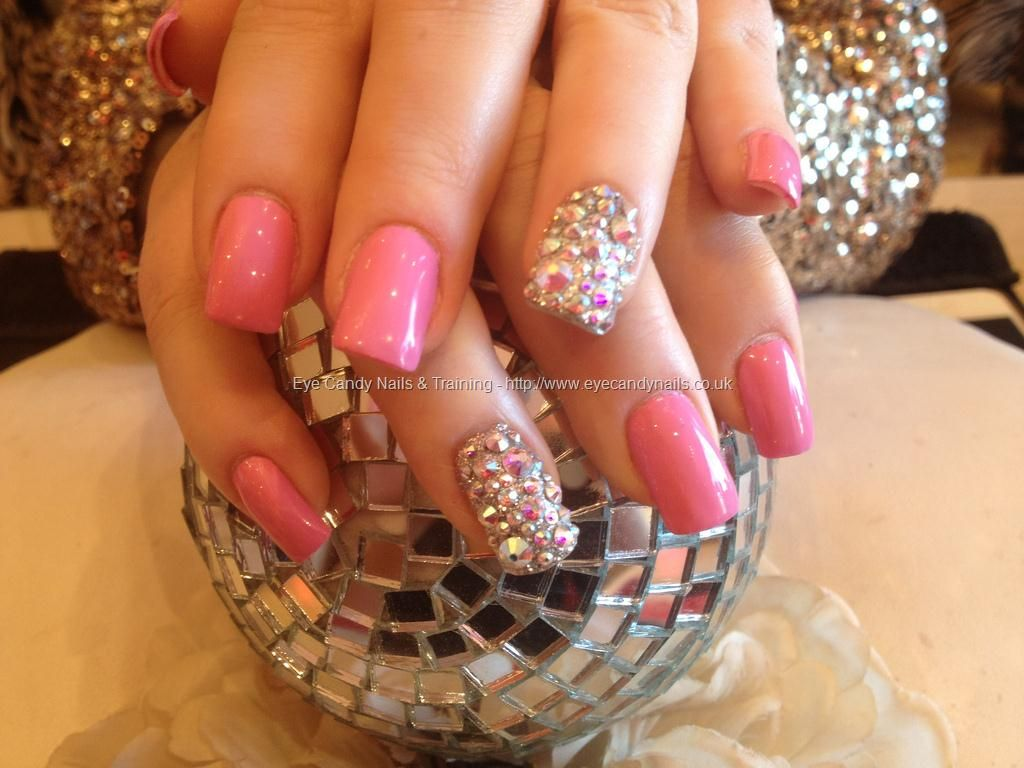 Acrylic nails with pink polish and Swarovski crystals on ring finger ...